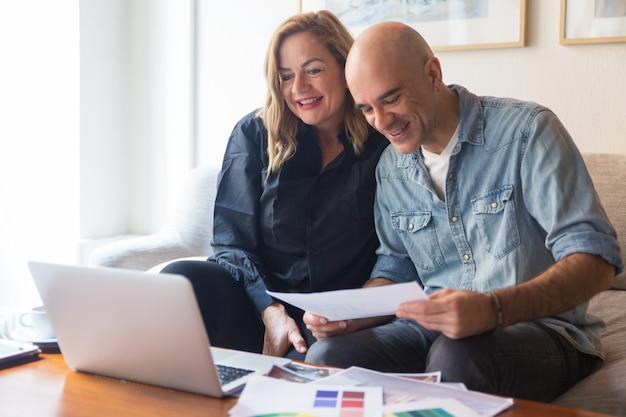 Feliz pareja de clientes hablando con el diseñador de interiores