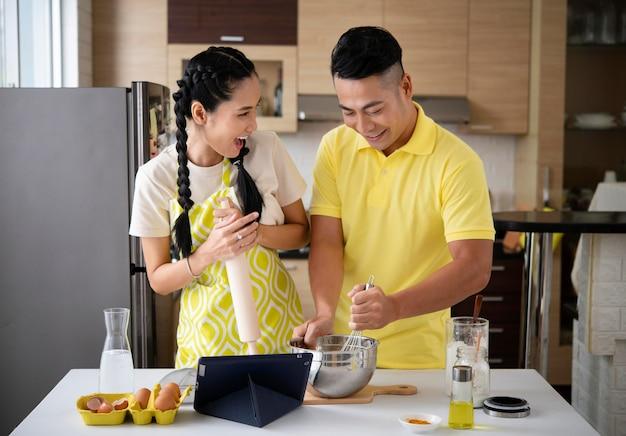 Feliz pareja cocinando en la cocina