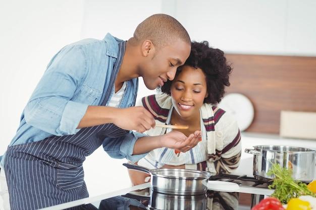 Feliz pareja cocinando juntos en la cocina