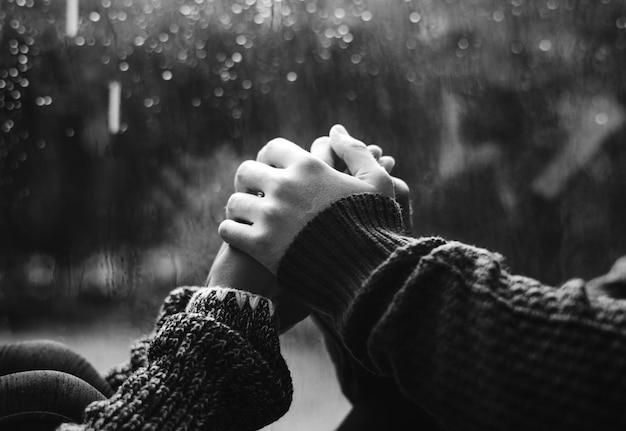 Feliz pareja cogidos de la mano por la ventana