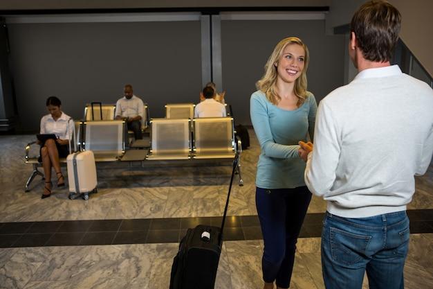 Feliz pareja cogidos de la mano mientras está de pie en la zona de espera