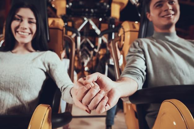 Feliz pareja cogidos de la mano en el parque de atracciones.