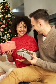 Feliz pareja compartiendo los regalos de navidad
