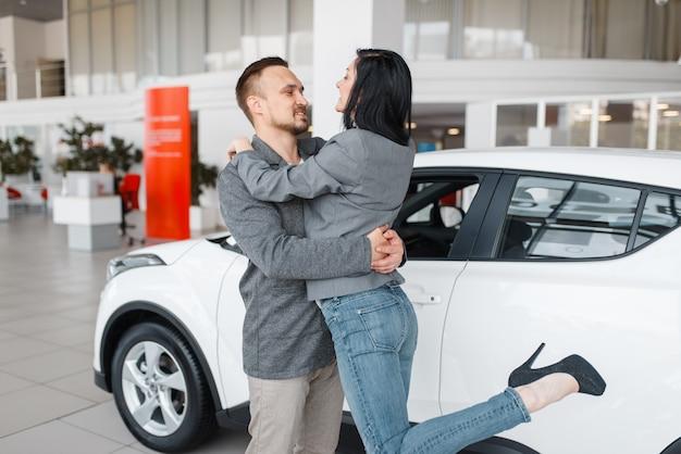 Feliz pareja comprando un coche nuevo en la sala de exposición, abrazos de hombre y mujer.