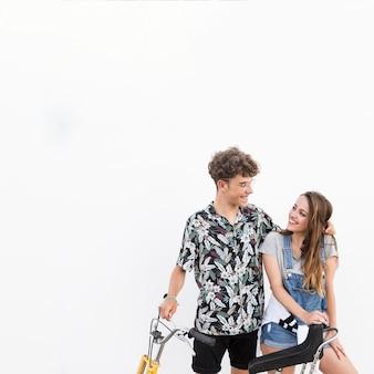 Feliz pareja con bicicleta mirando el uno al otro sobre fondo blanco