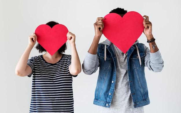 Feliz pareja con iconos de corazón rojo