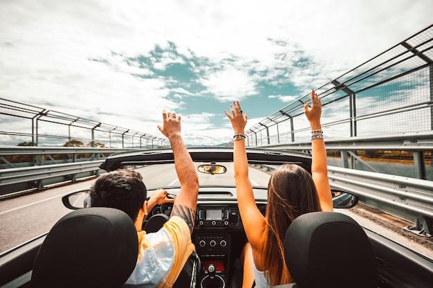 Feliz pareja conduciendo un auto convertible disfrutando de vacaciones divirtiéndose en la carretera