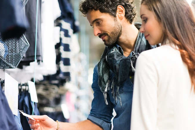 Feliz pareja de compras en una tienda de vestidos