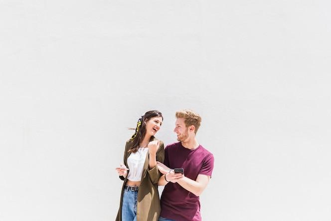 Feliz pareja de jóvenes con smartphone de pie contra el fondo blanco
