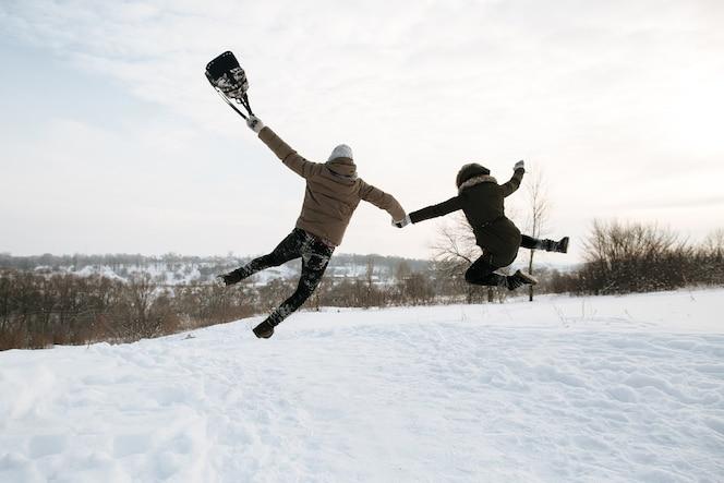 Feliz pareja de jóvenes en el amor está saltando de alegría. fría día de invierno cubierto de nieve. historia de amor de invierno.