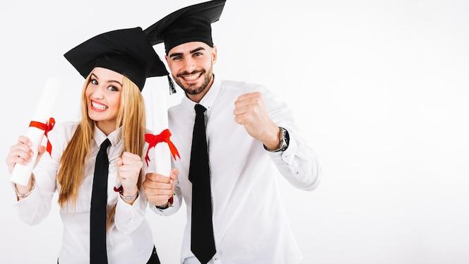 Feliz pareja de pie con diplomas