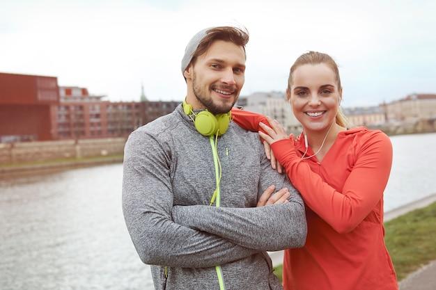 Feliz pareja deportiva posando contra el río