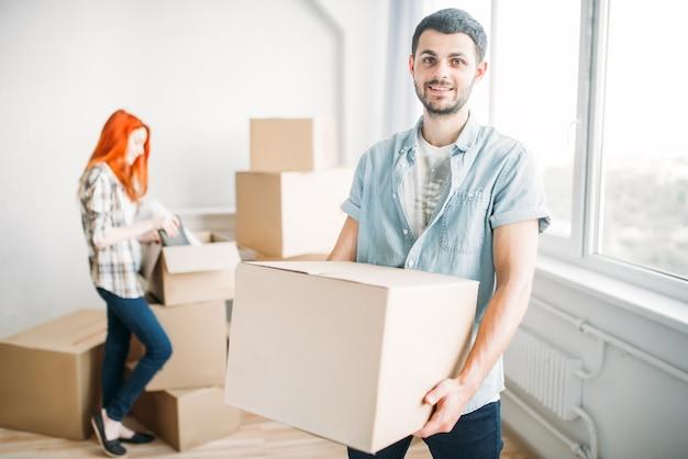 Feliz pareja desembalaje de cajas de cartón, inauguración de la casa. mudarse a una nueva casa