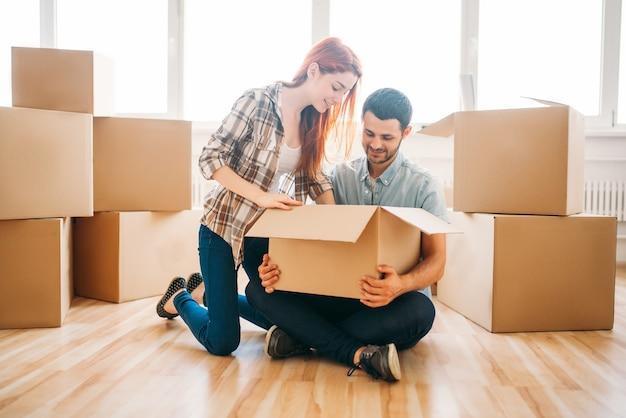 Feliz pareja desembalaje de cajas de cartón con propiedad, inauguración de la casa. mudarse a una nueva casa