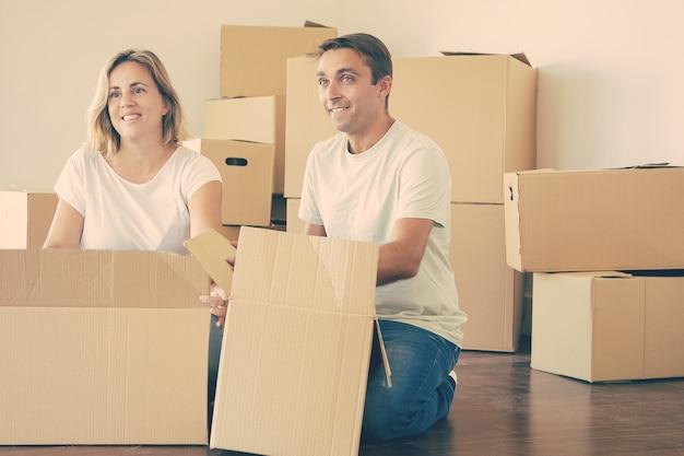 Feliz pareja desembalaje de cosas en apartamento nuevo, sentados en el suelo con cajas abiertas, mirando a otro lado