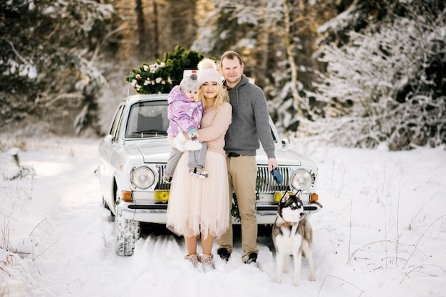 Feliz pareja en un día de invierno con coche retro y husky