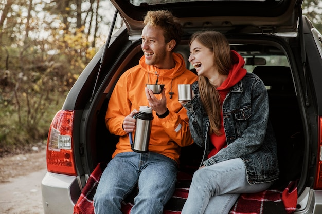 Feliz pareja disfrutando de una bebida caliente en el maletero del coche