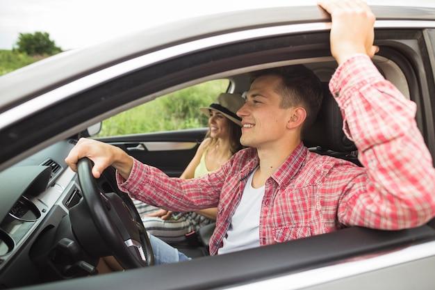 Feliz pareja disfrutando de viajar en el coche