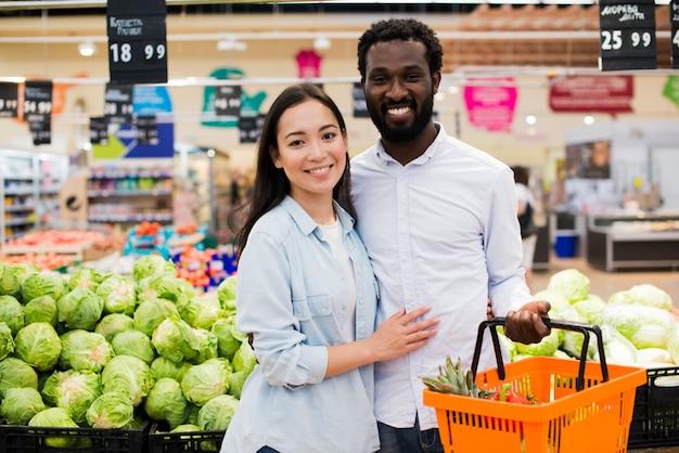 Feliz pareja diversa en la tienda de comestibles
