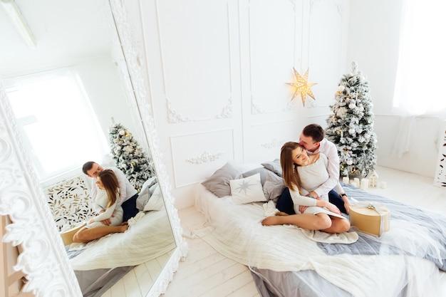 Feliz pareja divertirse en la habitación con un gran espejo y árbol de navidad
