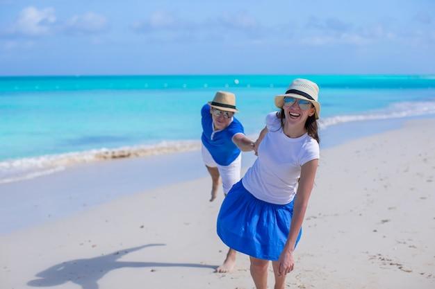 Feliz pareja divertirse durante las vacaciones en la playa del caribe