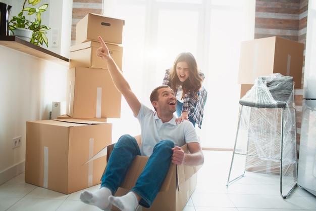 Feliz pareja se divierte con cajas de cartón en casa nueva en día de mudanza
