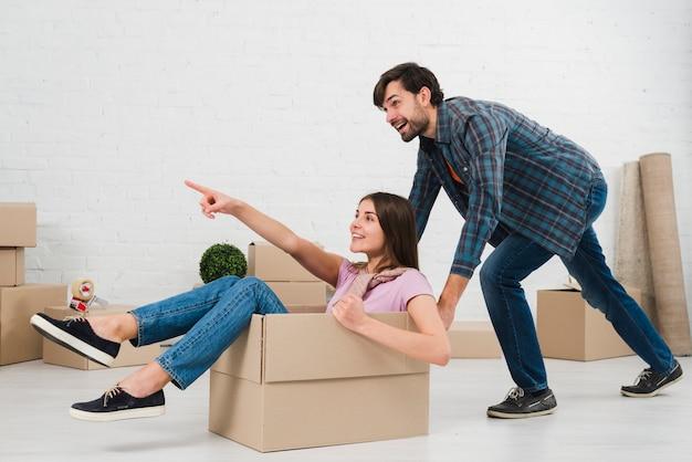 Feliz pareja se divierte con cajas de cartón en casa nueva
