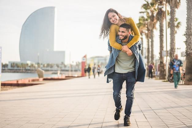 Feliz pareja divirtiéndose caminando en barcelona