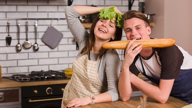 Feliz pareja divirtiéndose con comestibles
