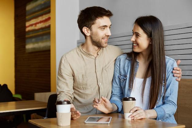 Feliz pareja de dos elegantes estudiantes sentados en la cafetería, tomando café, sonriendo, abrazándose y hablando de su vida.