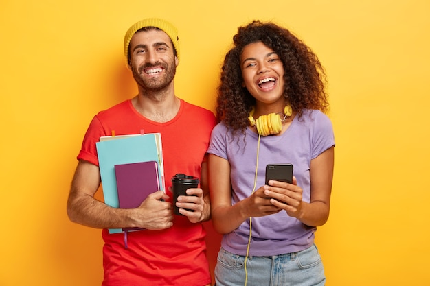 Feliz pareja elegante posando contra la pared amarilla con gadgets