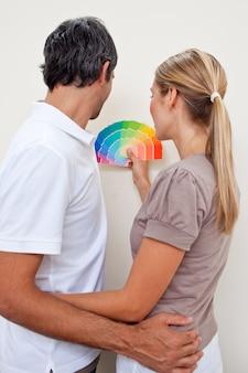 Feliz pareja elegir un color para pintar su dormitorio