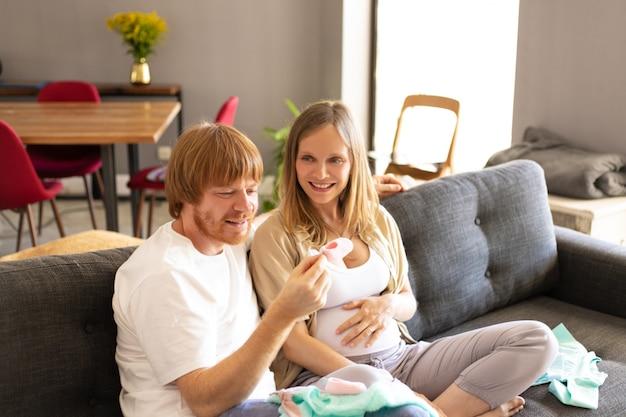 Feliz pareja embarazada comprobando la ropa del bebé en la sala de estar