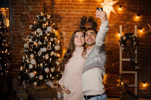 Feliz pareja embarazada haciendo selfie en el fondo del árbol de navidad