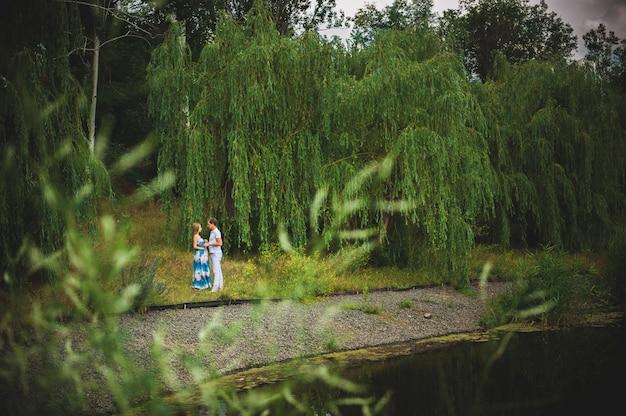 Feliz pareja embarazada en el parque de verano