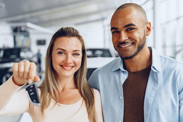 Feliz pareja emocionada comprando un coche nuevo y mostrando las llaves