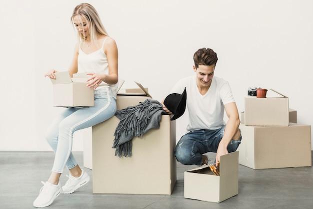 Feliz pareja empacando ropa en cajas