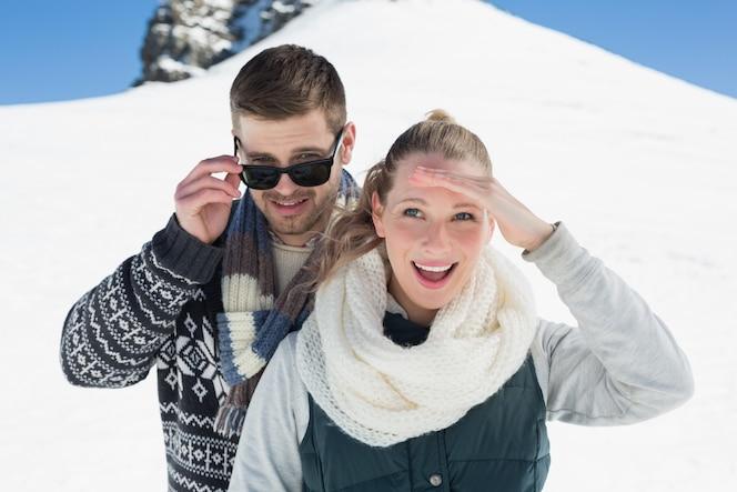 Feliz pareja en ropa de abrigo frente a la colina nevada