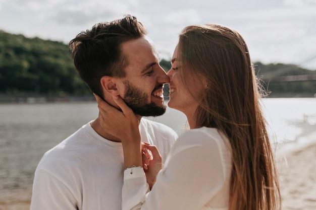 Feliz pareja de enamorados abrazándose y besándose juntos en la playa en un cálido día soleado