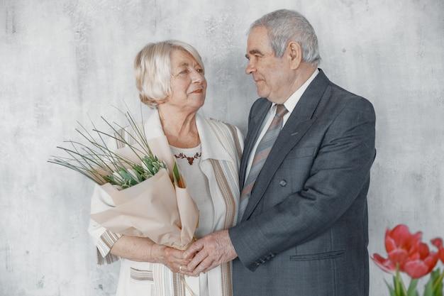 Feliz pareja de enamorados abrazándose, marido y mujer de pelo gris. mujer mayor que sostiene un ramo de flores.