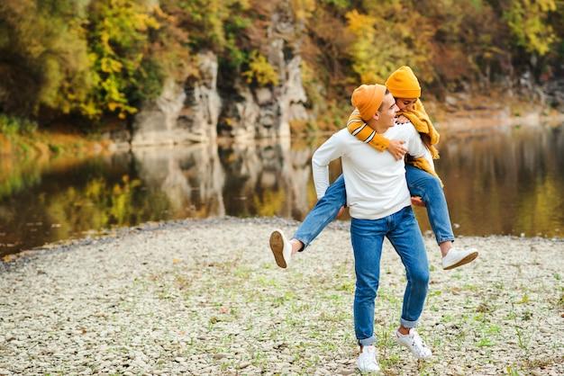Feliz pareja de enamorados caminando en un hermoso día de otoño. moda de otoño. chica guapa con estilo con novio divirtiéndose juntos en la naturaleza. humor de otoño