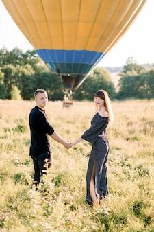 Feliz pareja de enamorados caminando juntos en el hermoso campo de verano, tomados de la mano y listos para tener un maravilloso viaje en globo aerostático