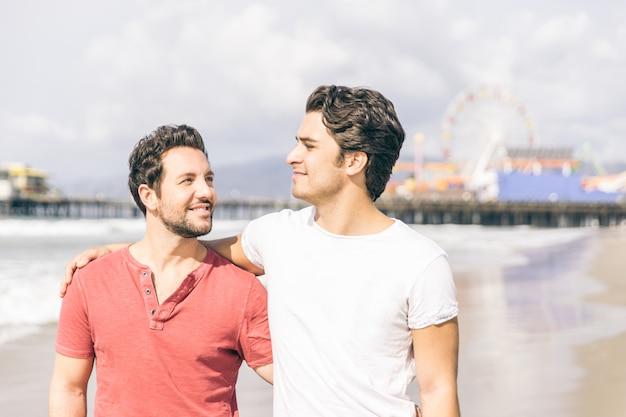 Feliz pareja de enamorados caminando por la playa