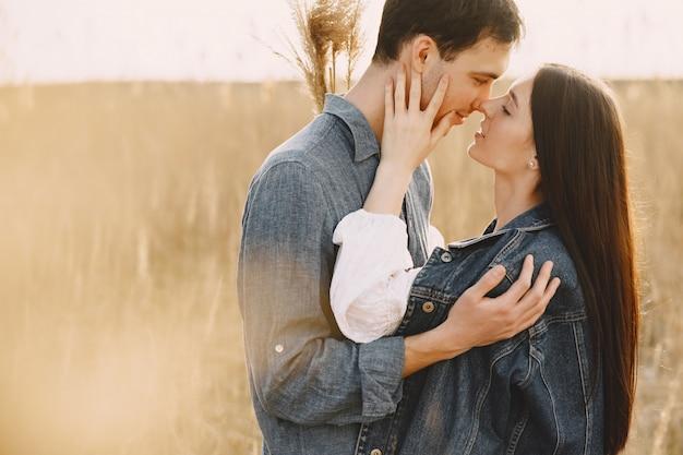 Feliz pareja de enamorados en el campo de trigo al atardecer