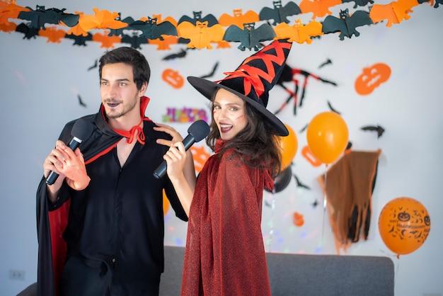 Feliz pareja de enamorados en disfraces y maquillaje en una celebración de halloween