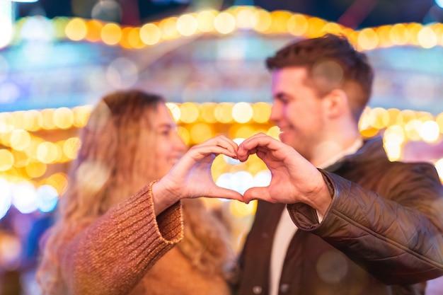 Feliz pareja de enamorados en el parque de atracciones haciendo forma de corazón con las manos