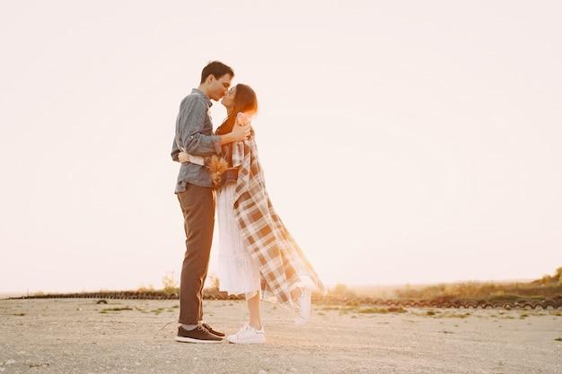 Feliz pareja de enamorados de pie en la calle al atardecer