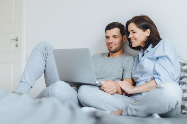 Feliz pareja de enamorados revisa sus fotos de boda en la computadora portátil