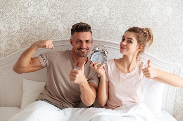 Feliz pareja encantadora sentados juntos en la cama con reloj despertador