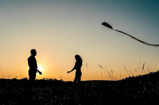 Feliz pareja encantadora en silueta volando cometa al aire libre